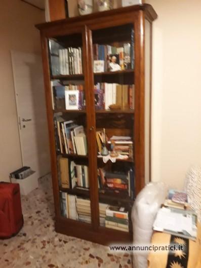 Mobile libreria con pareti e ante vetrate.